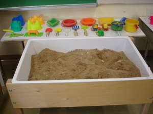 We chose to put out familiar sand tools and continue our extension of summer experiences with sand castle molds. All the materials are placed on a mat so children know where to put them when they are finished.