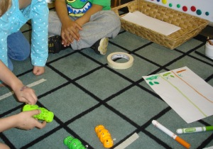 Racing caterpillars at the math centre. The children negotiated the length of the course and recorded the results of their races.