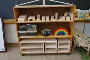 "Blocks and building materials. The rainbow is from Grimm (""Rainbow Stacker"") and provides endless opportunities for open ended play. The basket is full of carpet squares (different sizes) from Arts Junktion, there is also a basket of playskils (not visible)."